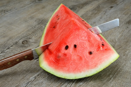 red and sweet watermelon sliced on wooden table photo