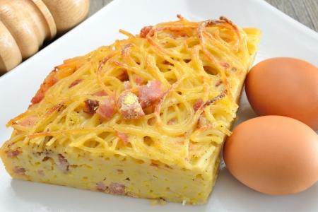 spaghetti frittata met eieren kaas en spek vervolgens gebakken in een pan