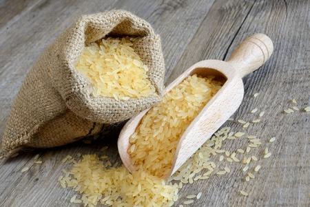 gepolijste rijst in zak ideaal voor salades en spade op houten tafel