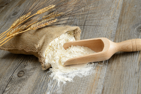 Wooden table with a sack of flour and spoon with ears Stock Photo