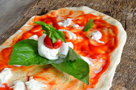 neapolitan: homemade pizza topped with tomato and basil ready to be cooked