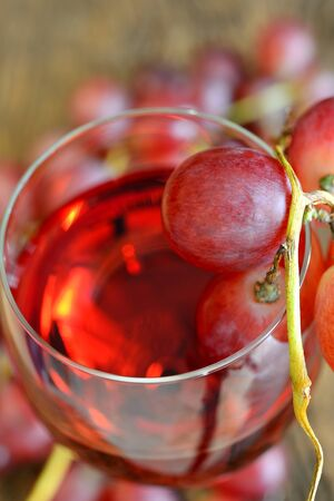 rose wine and grapes on old wooden table Stock Photo