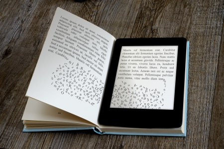 publishing: modern ebook reader on book on wooden background