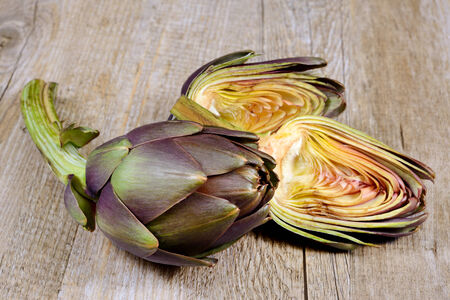 fresh  raw whole artichokes on wooden table