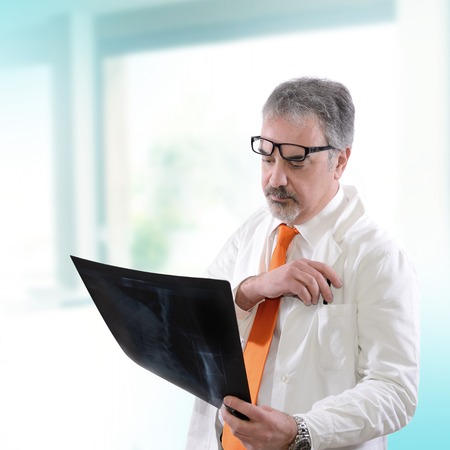 doctor looking an x-ray hospital for a diagnosis photo