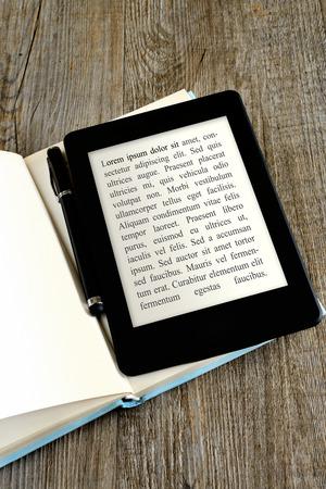 blanco pagina ebook reader op boek op houten achtergrond