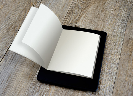 blank page ebook reader on book on wooden background