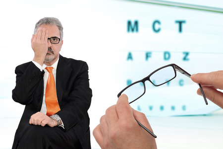 businessman checks the sight with his hand covering one eye