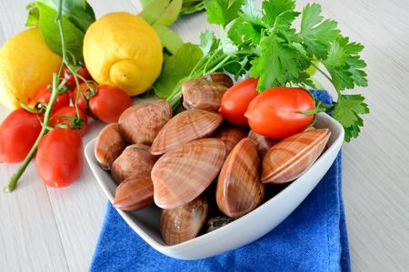 live again: raw sea fruits called fasolari live again with lemon
