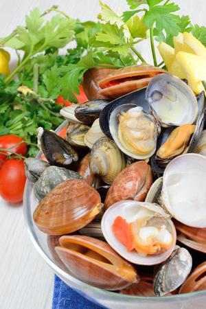 live again: raw sea fruits called fasolari live again with lemon and spaghetti pasta ingredients Stock Photo