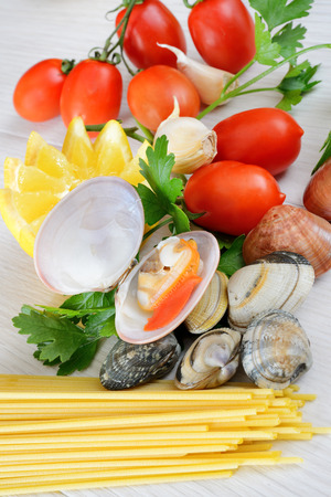raw sea fruits called fasolari live again with lemon and spaghetti pasta ingredients Stock Photo