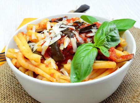 italian sicilian  homemade pasta with eggplant and pecorino cheese and tomato sauce called pasta alla norma Imagens
