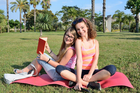 goofing: Two girl goofing around and read on a lawn in park