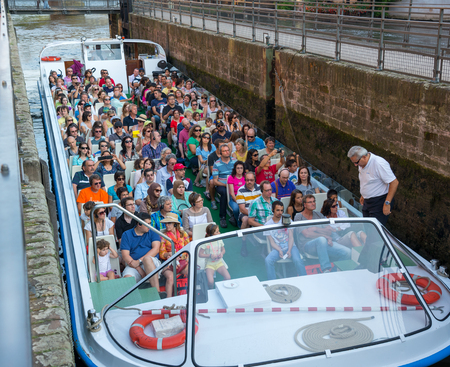 exceeds: STRASBOURG-AUGUST 1: tourists on the boat exceeds the slope of the dam Strasbourg August 1, 2014  in Strasbourg on August 1, 2014