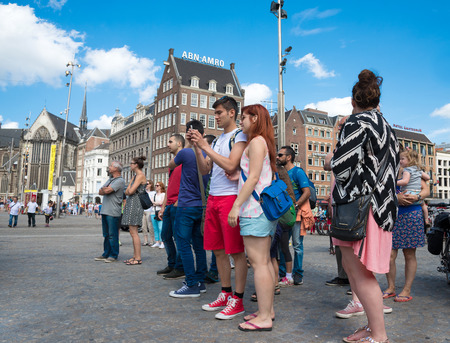 dam square: AMSTERDAM, CIRCA AUGUST 2014: Tourists take pictures in Dam Square.  Every year by about 4 million tourists circa  august 2014 in Amsterdam Editorial