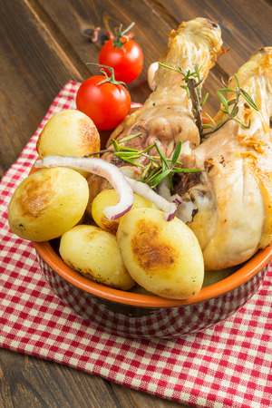 oven chicken: crispy chicken leg and little potatoes by oven Stock Photo