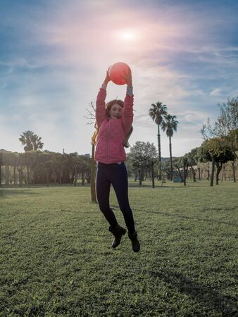 footing: young girl smiling and jumping in the park