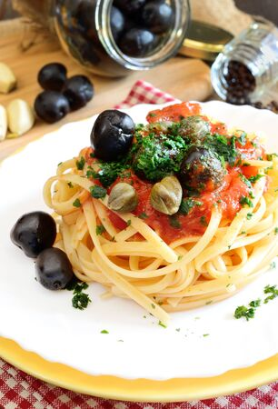 linguine pasta: linguine pasta with tomato sauce and black olives and capers Stock Photo