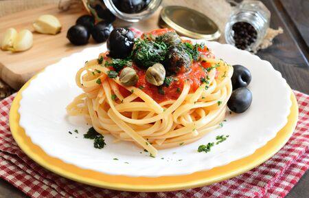 alcaparras: la pasta linguini con salsa de tomate y aceitunas negras y alcaparras Foto de archivo