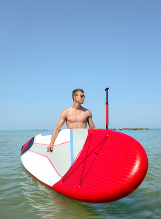 sup: Young attractive boy on Stand Up Paddle Board, SUP,in blu sea Stock Photo