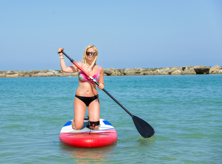 blu: Blonde woman on Stand Up Paddle Board, SUP,in blu sea