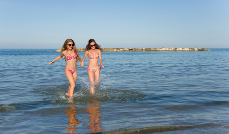 kids playing water: smiling girls splashing and running in the sea