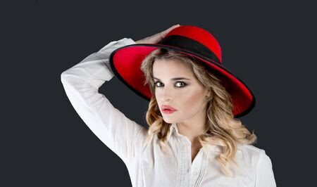 cute blonde: young woman whit red hat on black background