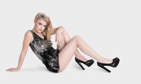 miniskirt: expressive beautiful blonde girl in miniskirt posing on white background Stock Photo