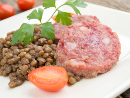 side dish of sausagecotechino  and lentils with parsley and tomato sweet