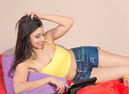 brunette woman on the bed working with tablet