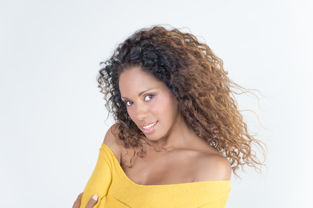 brazilian ethnicity: Brazilian smiling woman with curly hair and yellow sweater