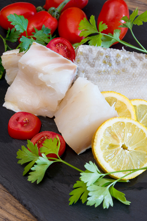 stockfish: Pieces of white raw salted  codfish with tomatoes and parsley on slate plate Stock Photo