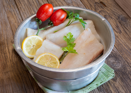 stockfish: Pieces of white raw salted  codfish with tomatoes and parsley on colander