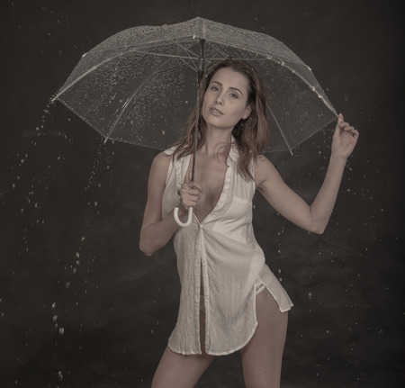 cute girl in nightgown on with umbrella and rain