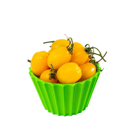 Sweet little yellow cherry tomatoes on green bowl on gray background
