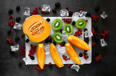 top view cutting board with fresh fruit on dark gray background with cold water drops and ice cubes Zdjęcie Seryjne