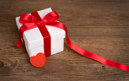 Gift box on the wooden background. Red ribbon. Valentines Day gift.