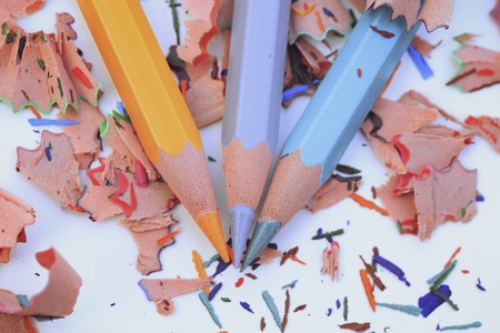 Colorful pencils and colorful wood shavings on white background