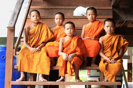 mea: Mea Hong Son, Thailand-August 17, 2015: Novice monks sitting on stairs at wooden monks house Stock Photo