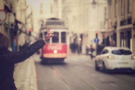 portugal: A traveler  calling one of the old tram in the center of Lisbon, Portugal in vintage style Stock Photo