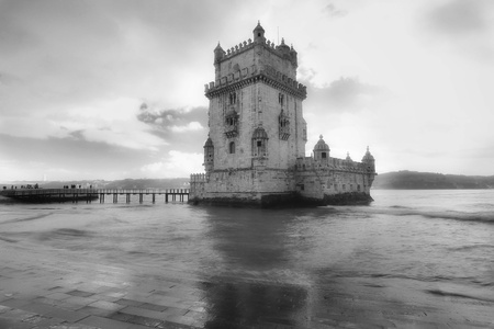 white: Belem Tower designed by architecture Francisco de Arruda with river Tagus Estuary on the back in black and white