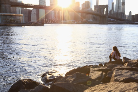 urban: Blurred of of a girl sitting on rocks with the view of Brooklyn Bridge and Manhattan Skyline at sunset in vintage color