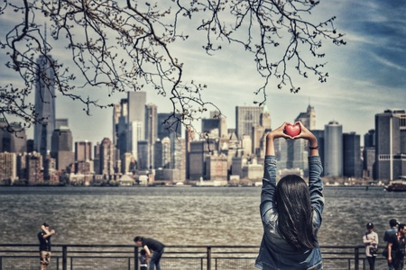 hands holding heart: Love concept, hands holding heart shape on Manhattan skyline background in vintage style Stock Photo