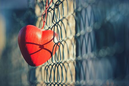 fence: Love concept, heart shape hanging on metal fence