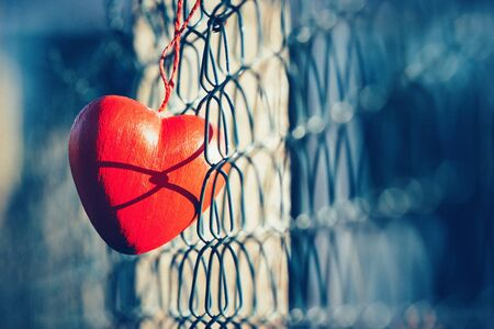 fence: Love concept, heart shape love symbol hanging on grid fence in vintage and grainy style