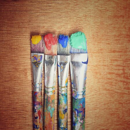 creative: Closeup of paintbrush on wooden background and heart shape around