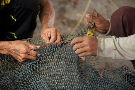 fishermans net: Selective focus on fishermans hand, repairing fishing net
