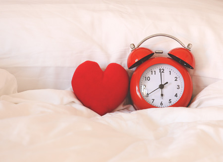 sleep well: Red alarm Clock and heart shape on white bed sheet against the pillow, sleep well concept Stock Photo