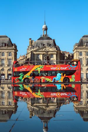 famous industries: Bordeaux, France, October 9, 2016 : Bordeaux is European Best Destination in 2015 - Touristic bus in Bordeaux at Place de la Bours with its reflection, city sightseeing.