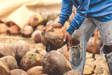 Man open coconut shell by old knife Stock Photo